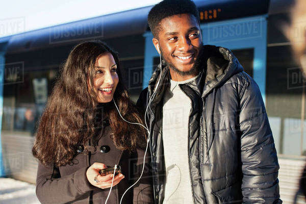 Happy young friends listening music through hands-free device against train Royalty-free stock photo