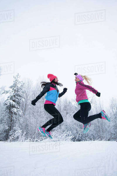 Side view of mid adult female friends jumping in winter Royalty-free stock photo