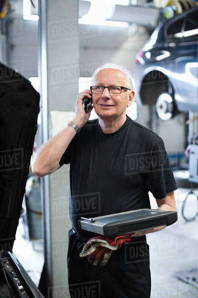 Senior male mechanic holding digital tablet looking away while using mobile phone at workshop Royalty-free stock photo