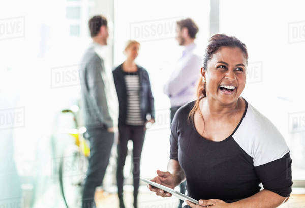 Happy businesswoman laughing while looking away with colleagues in background at office Royalty-free stock photo