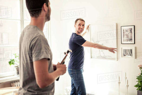 Side view of young gay man looking at partner while hanging frame on wall in home Royalty-free stock photo