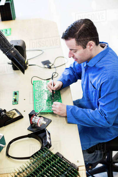 Mature male electrician working on circuit board at desk in factory Royalty-free stock photo