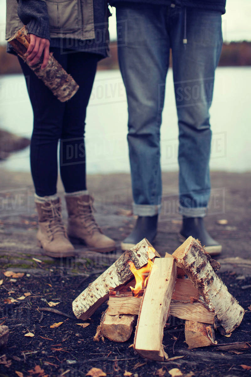 Low section of couple standing by bonfire Royalty-free stock photo