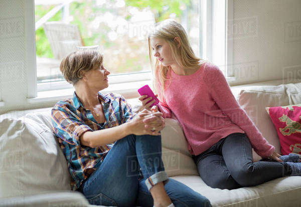 Mother and daughter conversing in living room Royalty-free stock photo