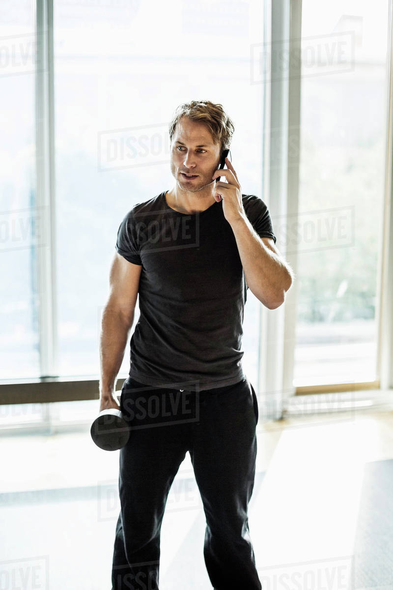 Man using mobile phone while exercising at gym Royalty-free stock photo