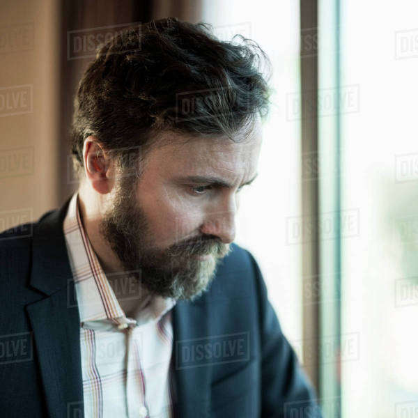Businessman looking down by window in hotel room Royalty-free stock photo