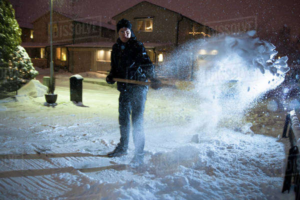 Full length of man removing snow from street Royalty-free stock photo