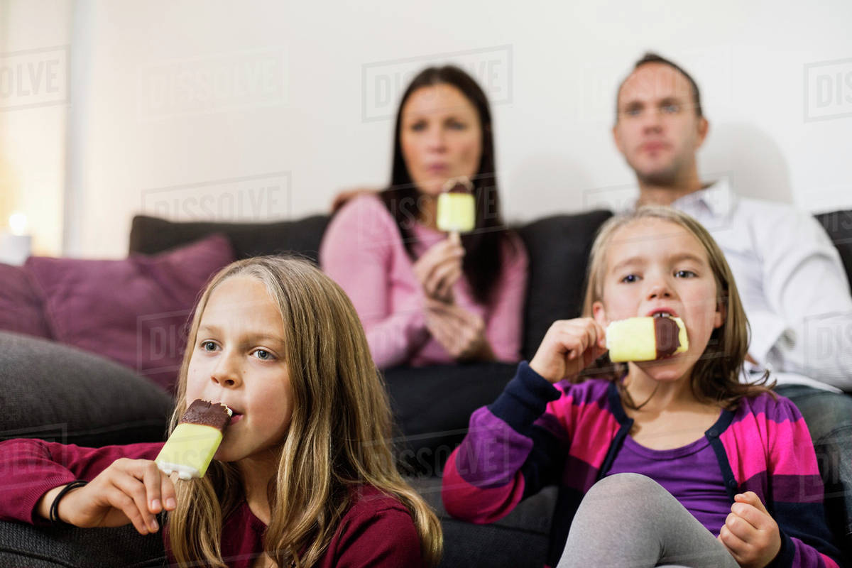 Family eating ice cream in living room - Stock Photo ...