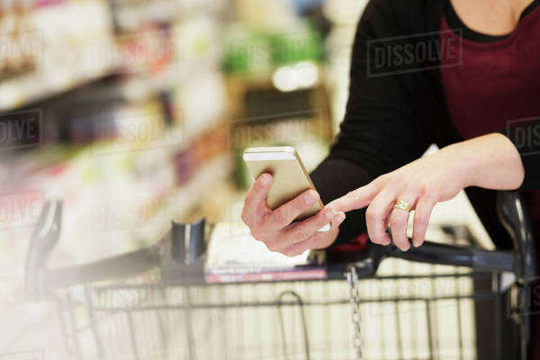 Midsection of woman checking shopping list in supermarket Royalty-free stock photo