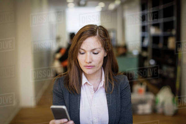 Businesswoman using mobile phone in office Royalty-free stock photo