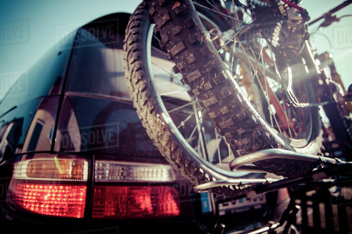 Cropped image of mountain bike tied to car Royalty-free stock photo