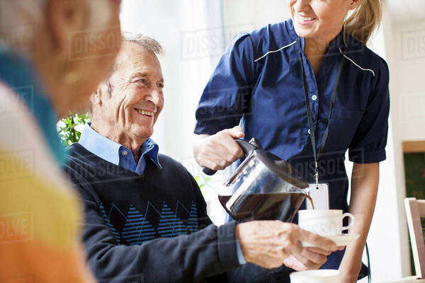 Midsection of happy female caretaker serving black coffee to senior man at nursing home Royalty-free stock photo
