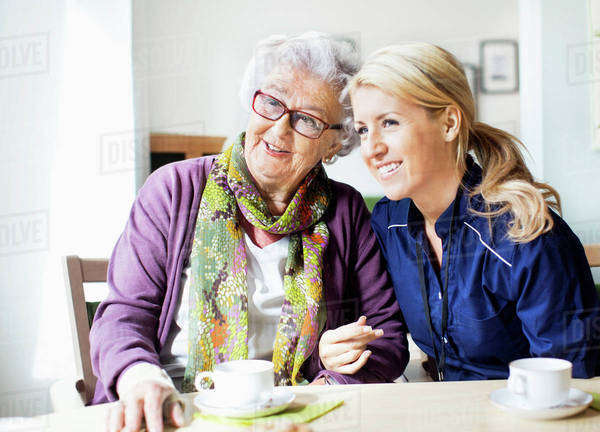Happy female caretaker and senior woman looking away while sitting at table in nursing home Royalty-free stock photo