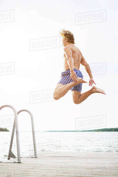 Full length rear view of man diving into lake against clear sky Royalty-free stock photo