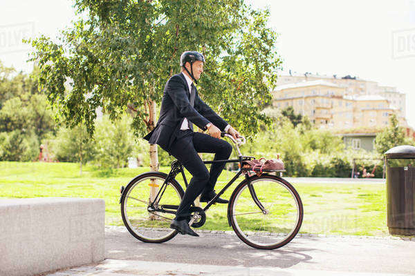 Full length of businessman riding bicycle in park Royalty-free stock photo