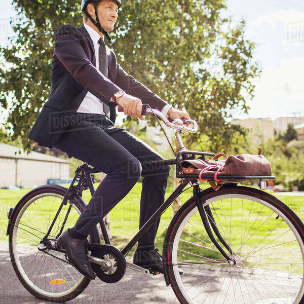 Businessman riding bicycle on street Royalty-free stock photo