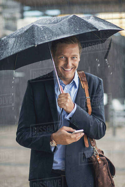 Portrait of smiling businessman using smart phone in city during rainy season Royalty-free stock photo