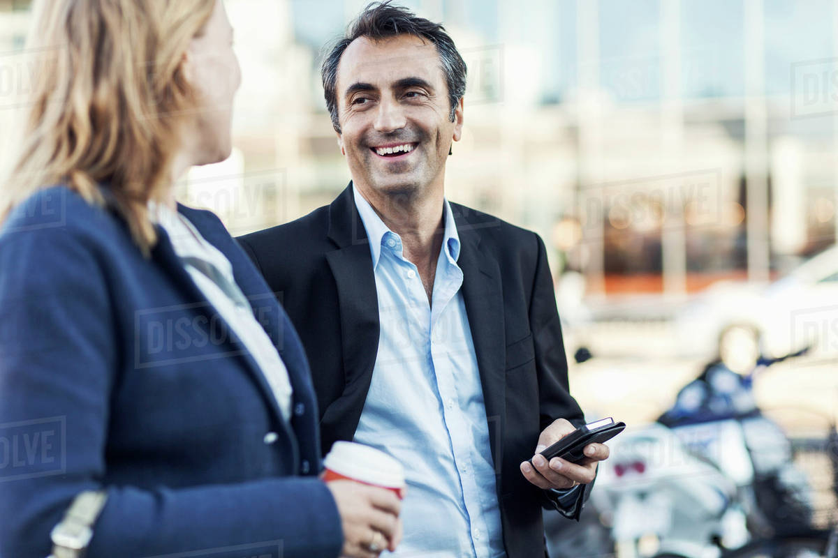 Happy businessman talking to female colleague outdoors Royalty-free stock photo