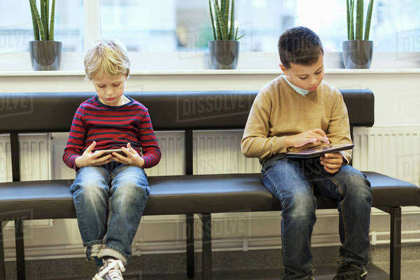 Boys using technologies while waiting at orthopedic clinic Royalty-free stock photo