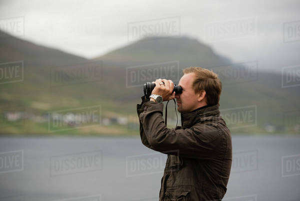 Side view of man using binoculars against mountain Royalty-free stock photo