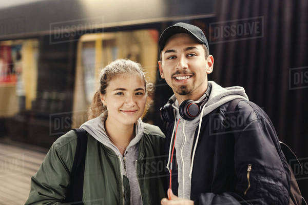 Portrait of happy young couple standing at subway station Royalty-free stock photo