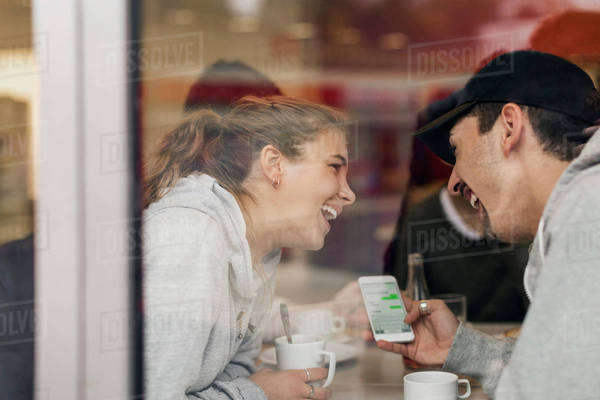 View of happy young couple using smart phone in cafe through glass Royalty-free stock photo