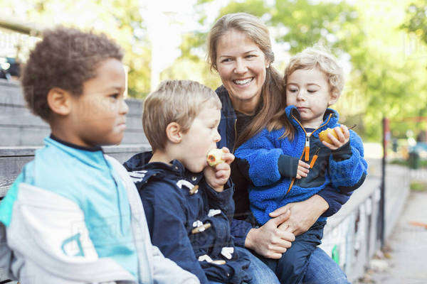 Happy teacher sitting with children outside kindergarten Royalty-free stock photo