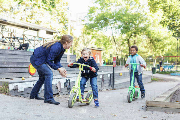 Teacher motivating children on push scooters during race Royalty-free stock photo