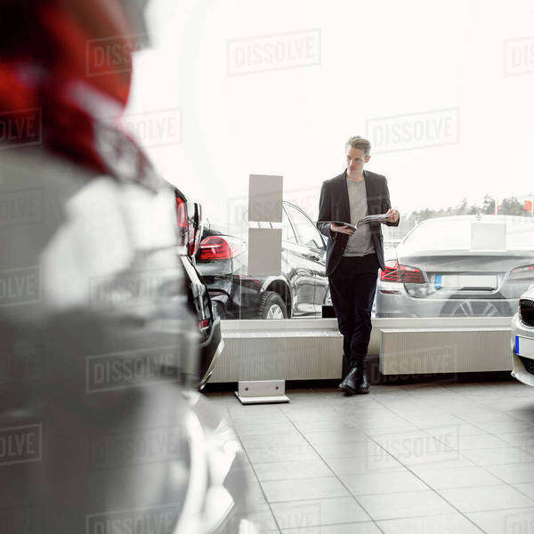 Full length of man reading brochure in car dealership store Royalty-free stock photo