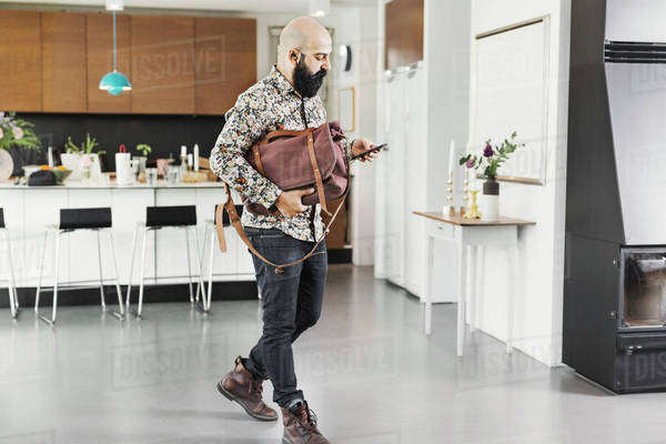 Full length of male architect with bag using mobile phone while walking in kitchen Royalty-free stock photo