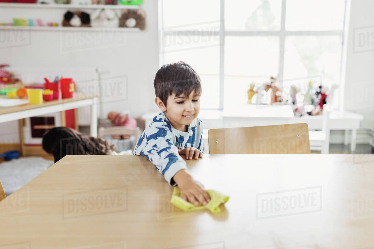 boy cleaning dining table at day care center stock photo dissolve
