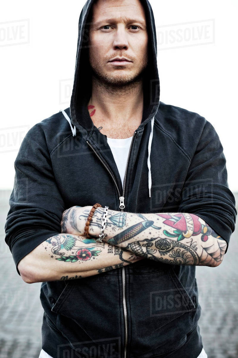 Portrait of a tattooed man in hooded jacket with arms crossed ...