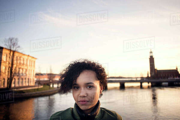 Portrait of teenage girl with curly short hair standing against canal in city Royalty-free stock photo
