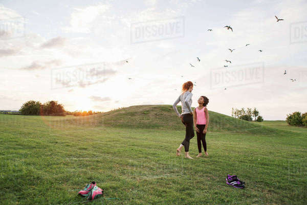 Mother and daughter standing together on grass at park against sky Royalty-free stock photo