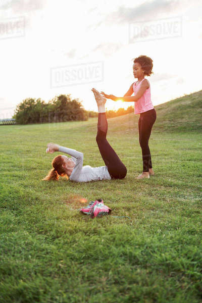 Girl helping mother exercising on grass at park against sky during sunset Royalty-free stock photo