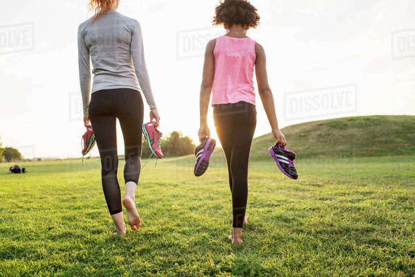 Rear view of mother and daughter holding sports shoes while walking on grass at park during sunset Royalty-free stock photo