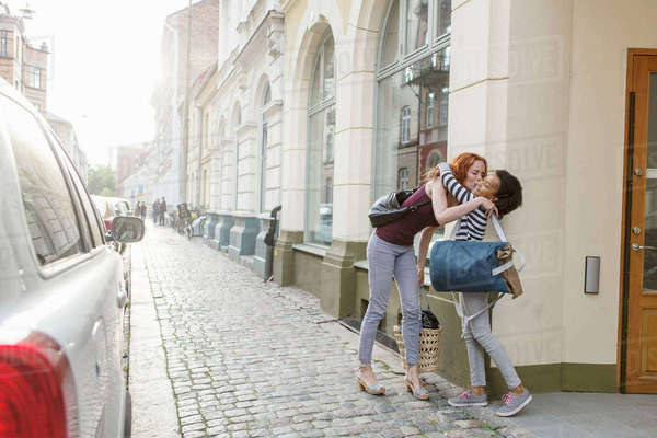 Mother kissing daughter on sidewalk against building in city Royalty-free stock photo