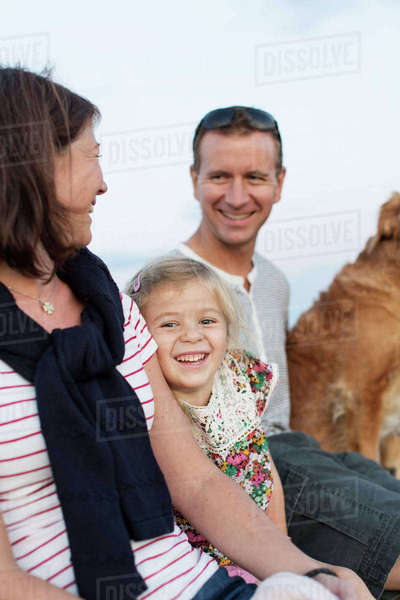 Cheerful girl sitting amidst father and mother with dog against sky Royalty-free stock photo