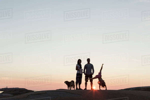 Father and mother looking at girl performing cartwheel on rock formation against sky during sunset Royalty-free stock photo