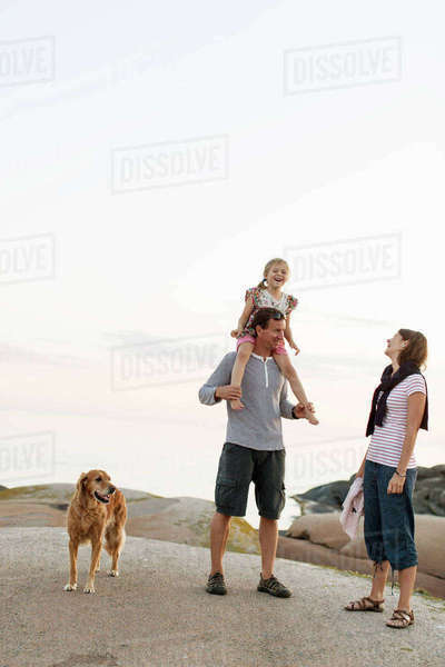 Mother looking at girl enjoying sitting on shoulder of father standing against sky Royalty-free stock photo
