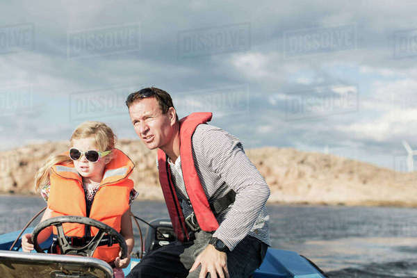 Girl driving motorboat with father in Baltic Sea against sky Royalty-free stock photo