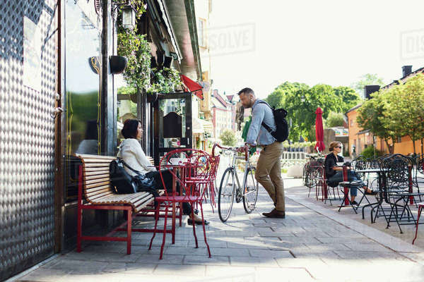 Full length of businessman with bicycle talking to colleague at sidewalk cafe Royalty-free stock photo