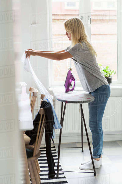 Full length of teenage girl ironing clothes against window at home Royalty-free stock photo