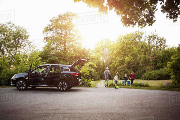 Open black electric car with family walking in park Royalty-free stock photo