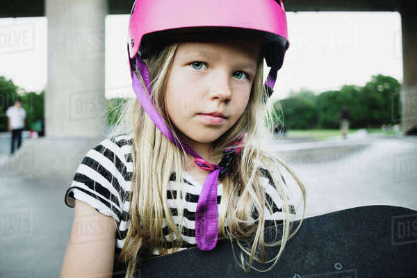 Portrait of girl wearing pink helmet holding skateboard at park Royalty-free stock photo