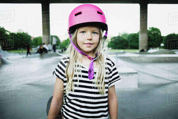 Portrait of smiling girl wearing pink helmet standing at skateboard park Royalty-free stock photo