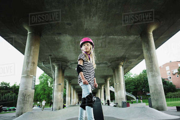 Low angle view of confident girl with skateboard standing at park Royalty-free stock photo