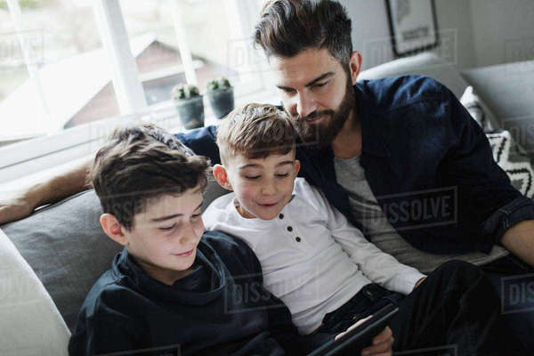 Tilt shot of father and son looking at boy using digital tablet in living room Royalty-free stock photo