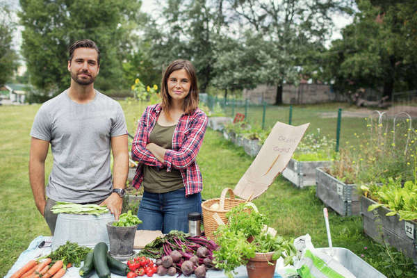 Portrait of mid adult couple standing at table full of freshly harvested garden vegetables Royalty-free stock photo