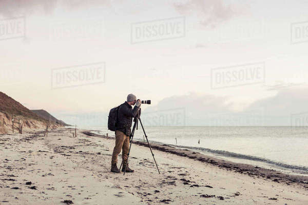 Full length side view of hiker photographing through SLR camera on shore at beach Royalty-free stock photo